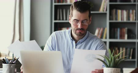 dokumentum : Serious young businessman checking corporate paperwork correspondence sitting at home office desk. Male entrepreneur reading documents, analyzing financial papers, preparing audit report at workplace. Stock mozgókép