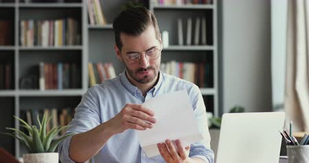 dokumentum : Excited male worker entrepreneur opening mail letter reading good news celebrating success. Happy businessman receiving loan approval, salary bonus, get promoted concept sitting at home office desk