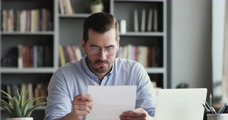 imposto : Angry stressed businessman opening envelope reading bad news in mail letter. Mad man feels frustrated about high bills, dismissal notice, bank debt, tax invoice or mistake sits at home office desk