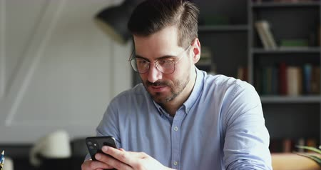 легкий : Smiling young man using smartphone indoors. Millennial businessman mobile technology user working in digital applications gadget searching information online, texting messages at home or in office.
