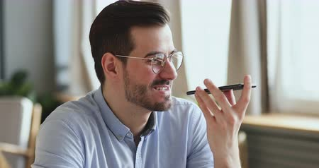 hang : Happy young man having mobile conversation on speakerphone. Smiling businessman recording audio message or using virtual ai assistant to search online on smart phone. Voice recognition tech concept.