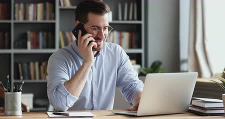 oturur : Smiling business man using laptop talking on cell phone sits at desk. Happy confident male professional manager web designer consulting client about online project making business call at workplace.