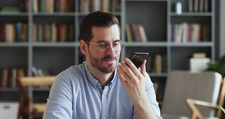 gravador : Smiling young man recording voice recognition message on speakerphone. Businessman using virtual assistant app sets reminder on smart phone at home office. Digital ai mobile assistance tech concept