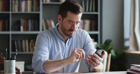 planlamacı : Male millennial professional holding modern smartphone texting message in office. Young businessman using helpful mobile apps for business time management organization concept sitting at work desk. Stok Video