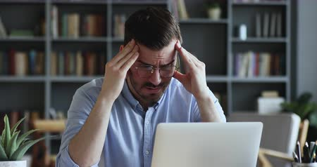 napětí : Stressed frustrated businessman wearing glasses suffering from headache at work. Exhausted tensed worker coping with migraine, emotional stress concept feeling pain sitting at office desk with laptop.