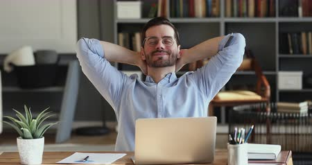 растягивание : Relaxed businessman takes break to relieve stress. Satisfied happy male employee meditating sitting at workplace desk holding hands behind head. Office worker finished work feels peace of mind concept