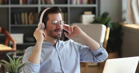 закрытыми глазами : Happy lazy office worker listening music in office. Smiling businessman wears wireless headphones enjoys stress free break sitting at work. Relaxed employee feels peace of mind at workplace concept