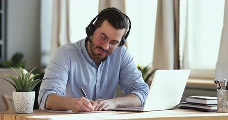 előléptetés : Smiling businessman wear wireless headset making conference video call on laptop. Male professional call center agent, hr manager having distance webcam chat job interview on computer in office. Stock mozgókép