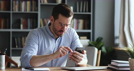 emperrado : Mad unhappy businessman feeling annoyed using smart phone. Angry businessman having problem with mobile spam message. Male user frustrated by low battery or bad signal concept sitting at office desk. Vídeos