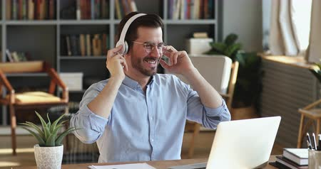 líný : Funny happy young businessman wears wireless headphones having fun listening music. Smiling employee feels no stress at work pretending playing guitar. Cheerful man enjoys relaxing at home office desk