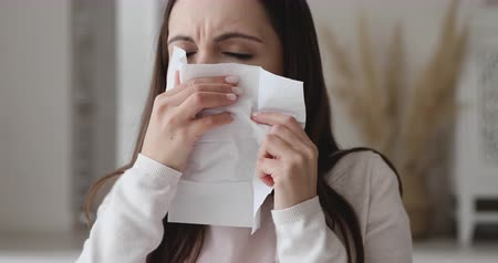 zsebkendő : Ill allergic young woman sneezing in tissue blowing running nose. Sick girl got flu concept or caught cold, having allergy symptoms. Unhealthy lady suffer from seasonal virus disease. Close up view Stock mozgókép