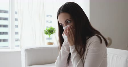 respiratory infection : Unhealthy young woman having allergic rhinitis suffering from snuffles. Ill sick girl holding tissue blowing stuffy nose caught cold sitting on sofa at home. Flu symptoms and chronic allergy concept