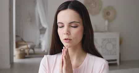 буддист : Young woman praying with hope holding hands clasped together. Mindful lady meditating with namaste mudra gesture and eyes closed. Spiritual religious teen girl says prayer concept, close up view