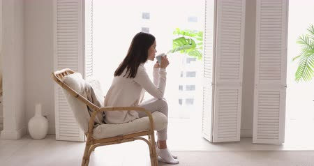 respiração : Relaxed young woman drinking tea looking through window enjoying peaceful lounge at home. Serene adult girl sitting in comfortable chair in cozy apartment dreaming, relaxing feeling no stress concept.