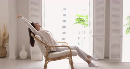 respiração : Happy healthy single young woman stretching sitting in wooden armchair. Relaxed satisfied lady feeling comfortable enjoying no stress peaceful quiet pleasant weekend in cozy apartment. Side view