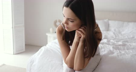 desperto : Depressed sick young woman feeling upset sitting alone on bed in the morning. Sad worried teen girl troubled with problem anxiety concept. Unhappy lady feel fatigue after sleepless night in bedroom.