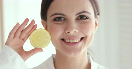citrón : Smiling pretty young woman holding lemon looking at camera. Happy healthy teen girl advertises fresh clean facial skin care treatment concept. Organic cosmetic fruit skincare mask. Close up portrait