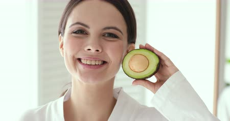 hidrasyon : Beautiful smiling girl holding avocado looking at camera. Happy pretty young woman advertising organic natural cosmetics for fresh clean facial skin care beauty treatment concept. Close up portrait Stok Video