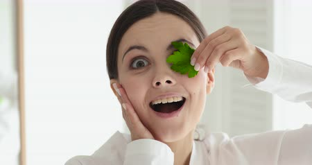 parsley : Excited funny girl vegan holding parsley looking at camera. Surprised happy young woman using green herbs for facial detox skin care treatment. Skincare organic cosmetics concept. Close up portrait