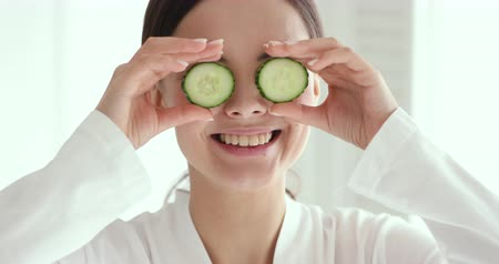 zelené oči : Funny happy young woman covering eyes with cucumbers advertising fresh clean healthy skin care concept. Cute teen girl holding organic vegetable spa mask laughing looking at camera. Close up portrait Dostupné videozáznamy