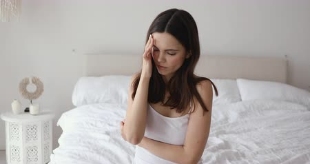 bezsennosć : Exhausted upset young woman sitting on bed suffering from morning headache concept. Sick lady insomniac touching head feeling migraine. Dizzy lady coping with hangover weakness alcohol withdrawal.