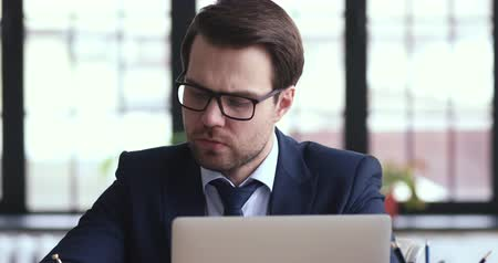 estratégico : Serious thoughtful businessman wearing suit solving business problems working on laptop making notes. Busy concerned ceo thinking of strategic plan, managing risks, doing market research concept. Stock Footage