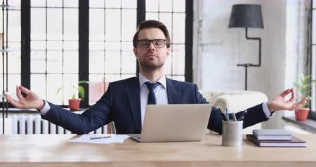 薬と健康管理 : Funny calm businessman wearing suit meditating sitting at desk. Mindful male ceo relaxing at workplace reducing work stress feels mental balance, relief and zen doing yoga exercise in office concept. 動画素材