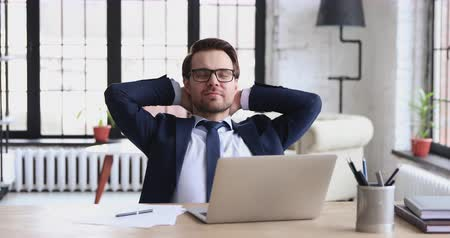 растягивание : Successful happy businessman executive relaxing satisfied with work well done sitting at desk. Smiling relieved ceo wearing suit feeling peace of mind at workplace concept holding hands behind head.