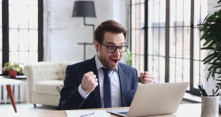 investidor : Overjoyed professional businessman executive celebrates online project business success receiving good news in email. Euphoric man entrepreneur triumphant looks at laptop rejoices victory achievement.