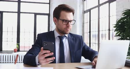 organisateur : Serious businessman using laptop computer and modern smartphone in office. Smart executive multitasking checking synced apps at work. Mobile and pc technology data synchronization for business concept