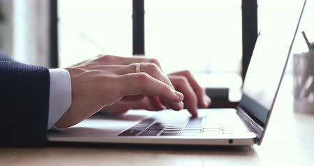 usuario : Close up view of male hands using laptop. Businessman wearing suit typing on computer keyboard browsing internet, communicating online, working on modern tech in office. Business software concept. Archivo de Video