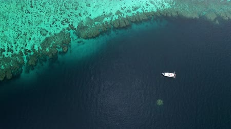 csökkenti a : A drone shot of oceans and a white ship. The drone reduces its speed as it lowers the height of its flight.