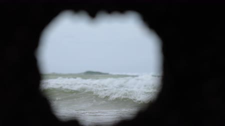 deterioration : View of the waves breaking on the shore, seen through a rusted porthole of a shipwreck.