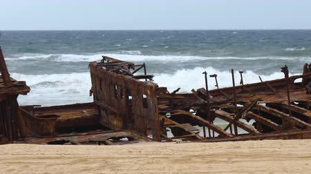 deterioration : Panning shot of a very rusted shipwreck on an Australian beach with a sign in front of it saying danger.