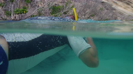 A shot of a man that wore his snorkeling mask and swims afterwards. Dostupné videozáznamy