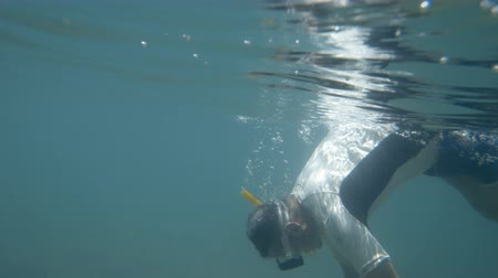 A shot of a diver afloat from the deep blue sea. The diver is wearing a white diving garment and a blue swimming shorts.