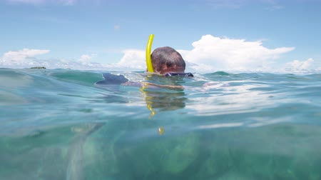 A close up shot of a snorkeler swimming its way to reach an inflatable float where his comrades are.