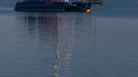 A medium shot of a boat and its reflection on the waters. Camera tilts up to show the boat
