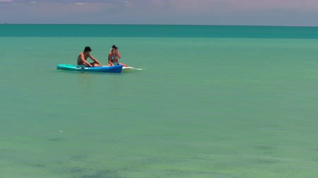 A full shot of a man and a woman kayaking on the ocean.