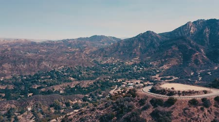 капитал : Cinema aerial panoramic video of the view of mountain formations in Malibu from a helicopter. The mountain road runs along the top of the hills. Los Angeles, California, USA