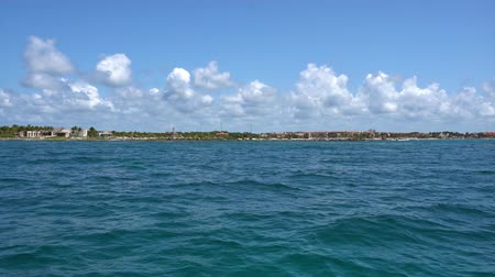 View of the shore from the boat on the waves in the warm Caribbean Sea. Riviera Maya Mexico. Summer sunny day, blue sky with clouds