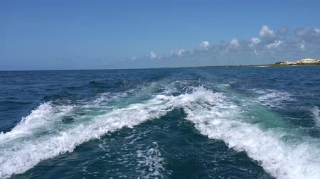 kruvazör : Trail on water surface behind of fast moving motor catamaran in the Caribbean Sea Cancun Mexico. Summer sunny day, blue sky with clouds