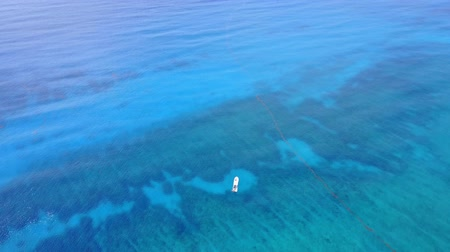 tyrkysový : Aerial drone shot. Flight over the beautiful bay. View of the boat in the distance from a birds eye view. Turquoise water of the Caribbean Sea. Riviera Maya Mexico.