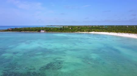 Aerial drone shot. Flight over the beautiful bay. A view of the coast from a birds eye view. The camera looks into the distance. Turquoise water of the Caribbean Sea. Riviera Maya Mexico.