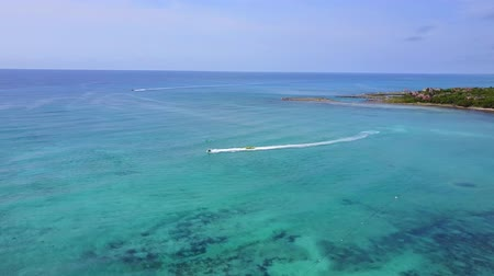 jet ski : Aerial drone shot. View from above of the water scooter with banana from a birds eye view. Turquoise water view coral coast of the Caribbean Sea. Riviera Maya Mexico.