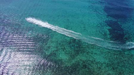jet ski : Aerial drone shot. View from above of the water scooters from a birds eye view. Turquoise water view coral coast of the Caribbean Sea. Riviera Maya Mexico. Stock Footage