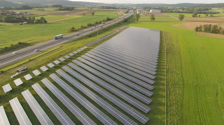 drone aerial of a solar power plant next to the highway in agricultural landscape