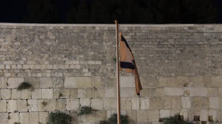 zsidó : State flag of Israel at the night on Western Wall background