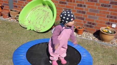 пять : Little girl (one year and five months old) is trying to jump on the trampoline