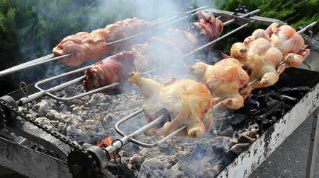 rosto : Rows of chickens cooking on a rotisserie, with charcoal and flame at outdoor.